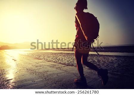 hiking woman on sunrise beach - stock photo