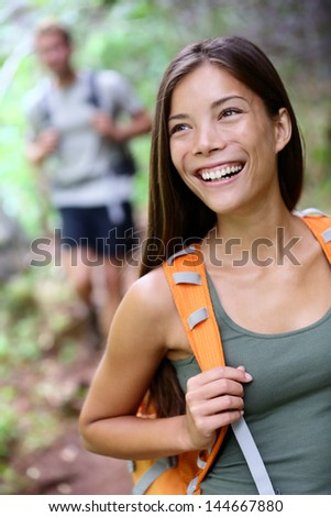 Hiking woman. Portrait of happy female hiker smiling looking away during hike trekking in forest wearing backpack. Asian girl in her twenties in Iao Valley State Park, Maui, Hawaii, USA. - stock photo