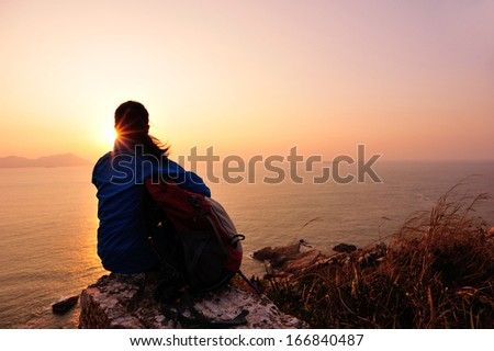 hiking woman sit on mountain rock watching the sunrise at the sea