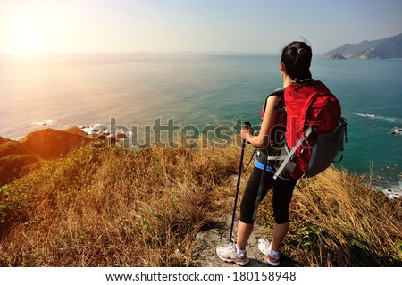 hiking woman stand under blue sky looking at the view