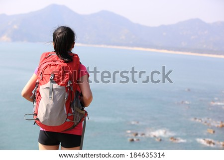 hiking woman stand under blue sky looking at the view - stock photo