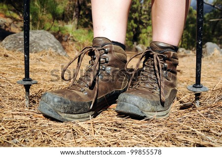 Hiking woman with trekking boots on the forest trail - stock photo