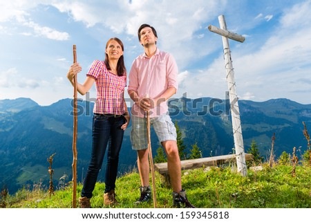 Hiking - Young couple standing on mountain summit at cross in the Bavarian Alps and enjoys the panorama in the leisure time or in vacation - stock photo
