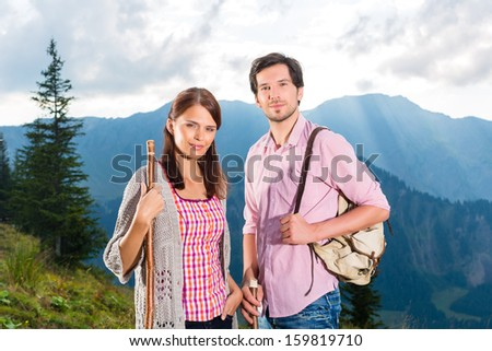 Hiking - Young couple standing on mountain summit in the Bavarian Alps enjoying the panorama in their leisure time or vacation - stock photo