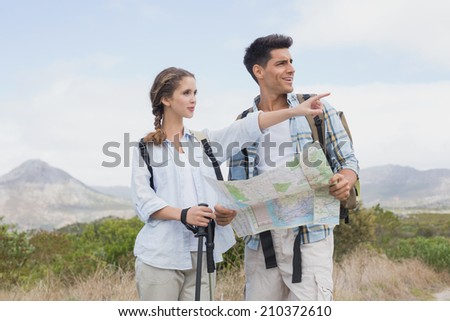 Hiking young couple with map pointing ahead on mountain terrain - stock photo