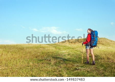 Hiking young woman with backpack and trekking poles walking on the meadow trail