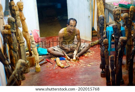 HIKKADUWA, SRI LANKA -FEB 02, 2012: Portrait of a wood carver at a souvenir market. Woodcarving is a traditional handicraft  in Sri Lanka. - stock photo