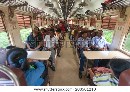 HIKKADUWA, SRI LANKA - FEBRUARY 22, 2014: Local commuters sit in train to Colombo. Trains are very cheap and poorly maintained but it's the best option to witness a bit of everyday local life. - stock photo