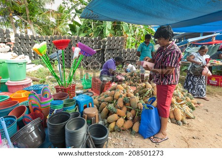 HIKKADUWA, SRI LANKA - FEBRUARY 23, 2014: Local woman buying from street vendor. The Sunday market is great way to see Hikkaduwa's local life come alive along with local delicacy