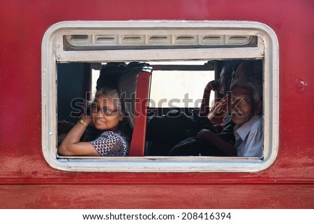 HIKKADUWA, SRI LANKA - MARCH 12, 2014: Commuters in train looking through window. Trains are very cheap and poorly maintained but it's the best option to witness a bit of everyday local life.