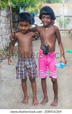 HIKKADUWA, SRI LANKA - MARCH 8, 2014: Local kids playing on the streets of Hikkaduwa village. These communities have tight knit bonds which show up in the streets. - stock photo