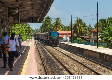 HIKKADUWA, SRI LANKA - MARCH 12, 2014: Train approaching Hikkaduwa train station. Trains are very cheap and poorly maintained but it's the best option to witness a bit of everyday local life. - stock photo