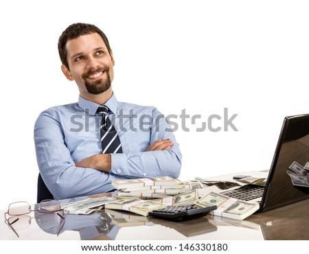hilarious businessman with arms crossed / cheerful and successful businessman at his desk with laptop and a lot of money - isolated on white background  - stock photo