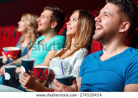 Hilarious film. Young cinema visitor hoot with laugh holding coke and popcorn. - stock photo