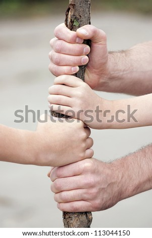 hildren's and adult hands keeping together - stock photo
