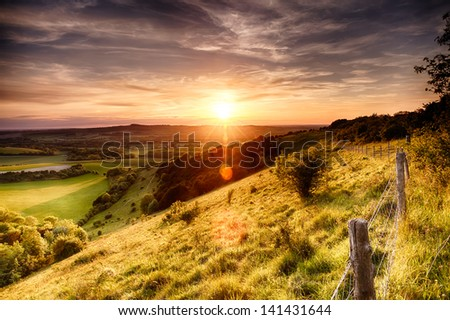 Hill fence landscape with evening sunset - stock photo