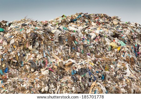 Hill of diverse domestic garbage in landfill  - stock photo
