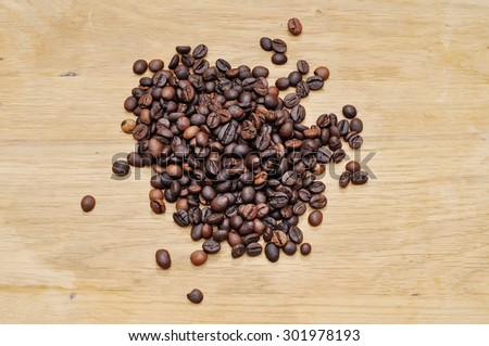 Hill of grains of coffee on a wooden surface.