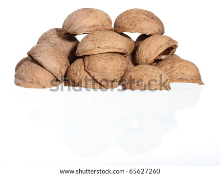 Hill of walnut's nutshells on white background with reflection