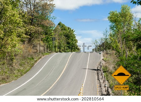 Hill on country road with yellow speed bump warning sign. - stock photo