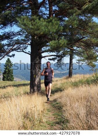 Hill running. Caucasian male runner athlete running in mountains. Summer, Pieniny, Poland. - stock photo