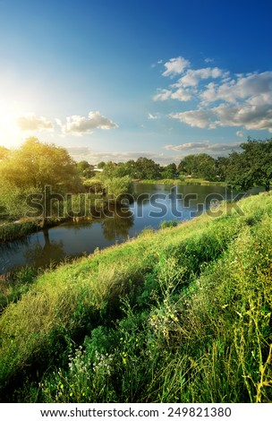 Hill with green grass near river at sunlight - stock photo