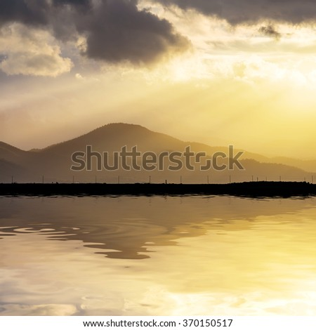 hills at the sunset reflected in a lake