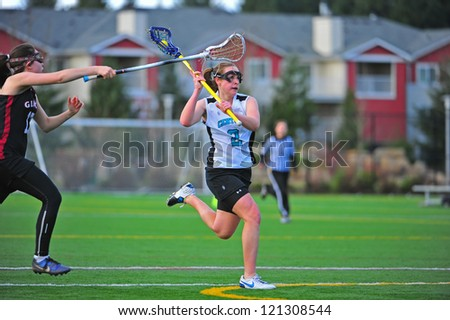 HILLSBORO, OR./USA - APRIL 25: Century Jag No. 2, Mareen Dunlop, moves in for a shot on goal as the Crimson tide tries to drown her. Final score 14-8 Century on APRIL 25, 2011 in Hillsboro, OR./USA. - stock photo