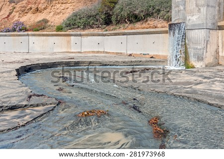 Hillside storm drain runoff on sandy beach. Flowing water makes a wet path in the sand.  - stock photo