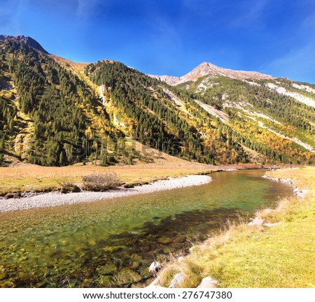 Hillsides picturesque alpine valley covered with thick coniferous forest. Quick stream of clear water flowing in the middle of the canyon - stock photo