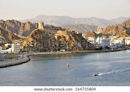 Hilltop fort on rocky outcrop overlooking the Muttrah Corniche and harbour in Muscat Oman - stock photo