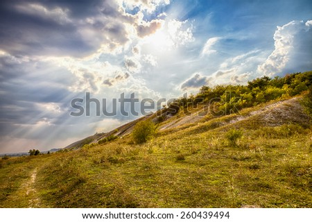 Hilly field and cloudy sky at sunset - stock photo