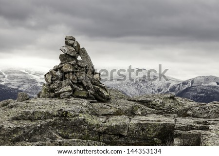 hilly landscape with a milestone of stones in the foreground - stock photo