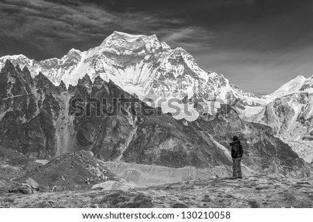 Himalayan guide on the trek to the background of the Gyachung Kang (7952 m) - Gokyo region, Nepal (black and white) - stock photo