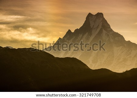 Himalayan mountain peak during sunrise ( Machapuchare or Fishtail peak in Nepal ) - stock photo