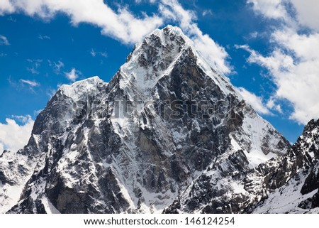 Himalayan mountains Cholatse and Tabuche Peak at the blue sky with clouds on a sunny day - stock photo