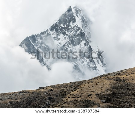 Himalayan peak in the clodly weather - Everest region, Nepal - stock photo