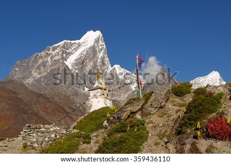 Himalayan peaks and Buddhist stupa with prayer flags - stock photo