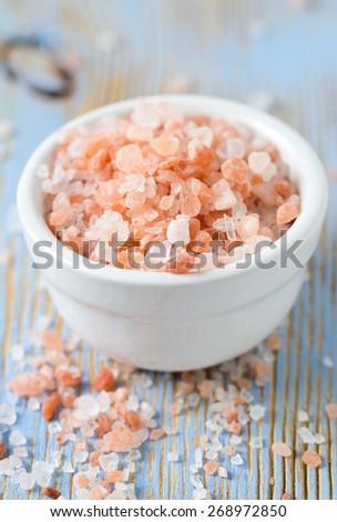 himalayan pink salt on wooden surface - stock photo