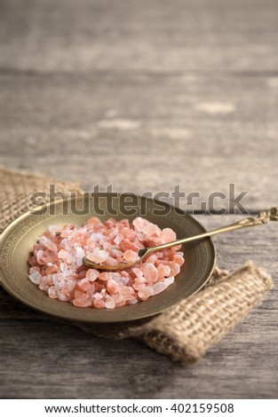Himalayan salt crystals on brass dish with burlap and wooden background - stock photo