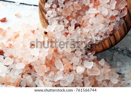 himalayan salt in wooden bowl on white background.