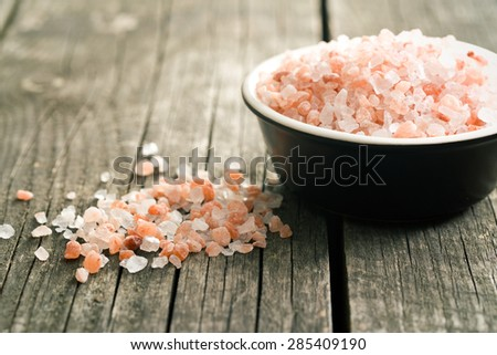 Himalayan salt on old wooden table - stock photo