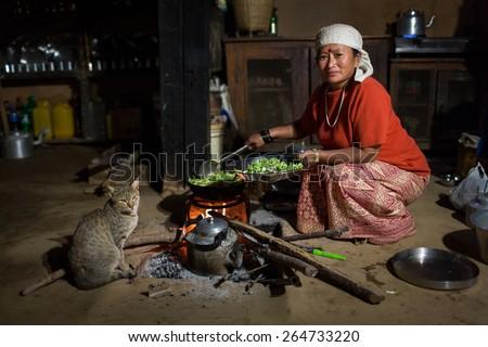 HIMALAYAN VILLAGE, NEPAL - NOVEMBER 24: Woman cooking inside of traditional house of Himalayan Village on November 24, 2014 in HIMALAYAN VILLAGE, Nepal - stock photo