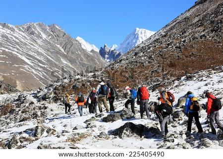 HIMALAYAS, NEPAL - MARCH, 2014: Group of tourists coming down from the mountains. Himalayas, Nepal. - stock photo
