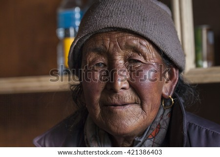 HIMALAYAS, NEPAL - OCTOBER 17, 2013: An unidentified old Nepalese woman with wrinkled face portrayed in a Himalayan village in Nepal