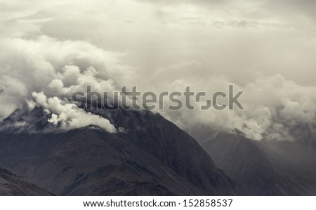 Himalayas. Snowy mountains in the clouds. Beautiful view from the Khardung La pass.