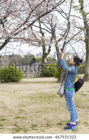 HIMEJI, JAPAN - MARCH 24, 2016:Tourists take pictures sakura, Himeji Castle in Japan.