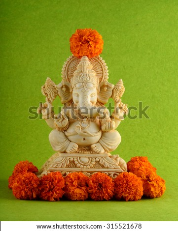 Hindu God Ganesha. Ganesha Idol on Green Background with flowers.  - stock photo
