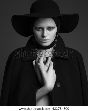 Hing fashion emotive portrait of young lady in black hat and coat. - stock photo