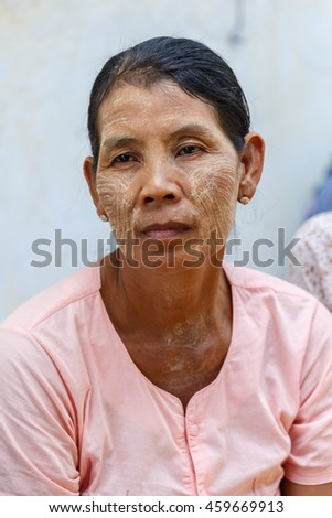 HINTHADA, MYANMAR - AUG 29:  Old burmese lady daubs thanaka on her face on Aug 29, 2015 in Hinthada, Ayeyarwady (Irrawaddy) Division, Myanmar.